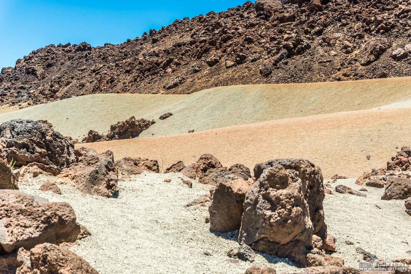 Verschiedenfarbige Sanddünen neben- und hintereinander.