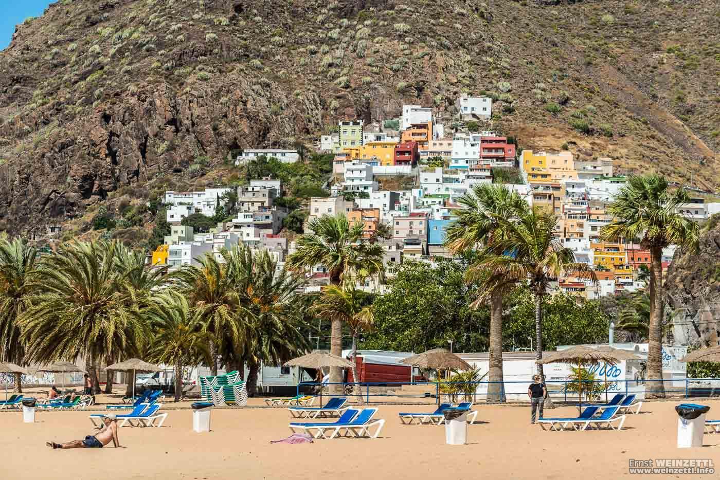 Hinter dem Strand und seinen Parkplätzen klebt ein Dorf im Felsen.